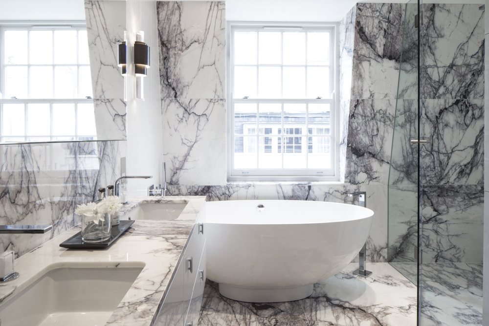 luxurious marble bathroom with marble vanity and round freestanding bath