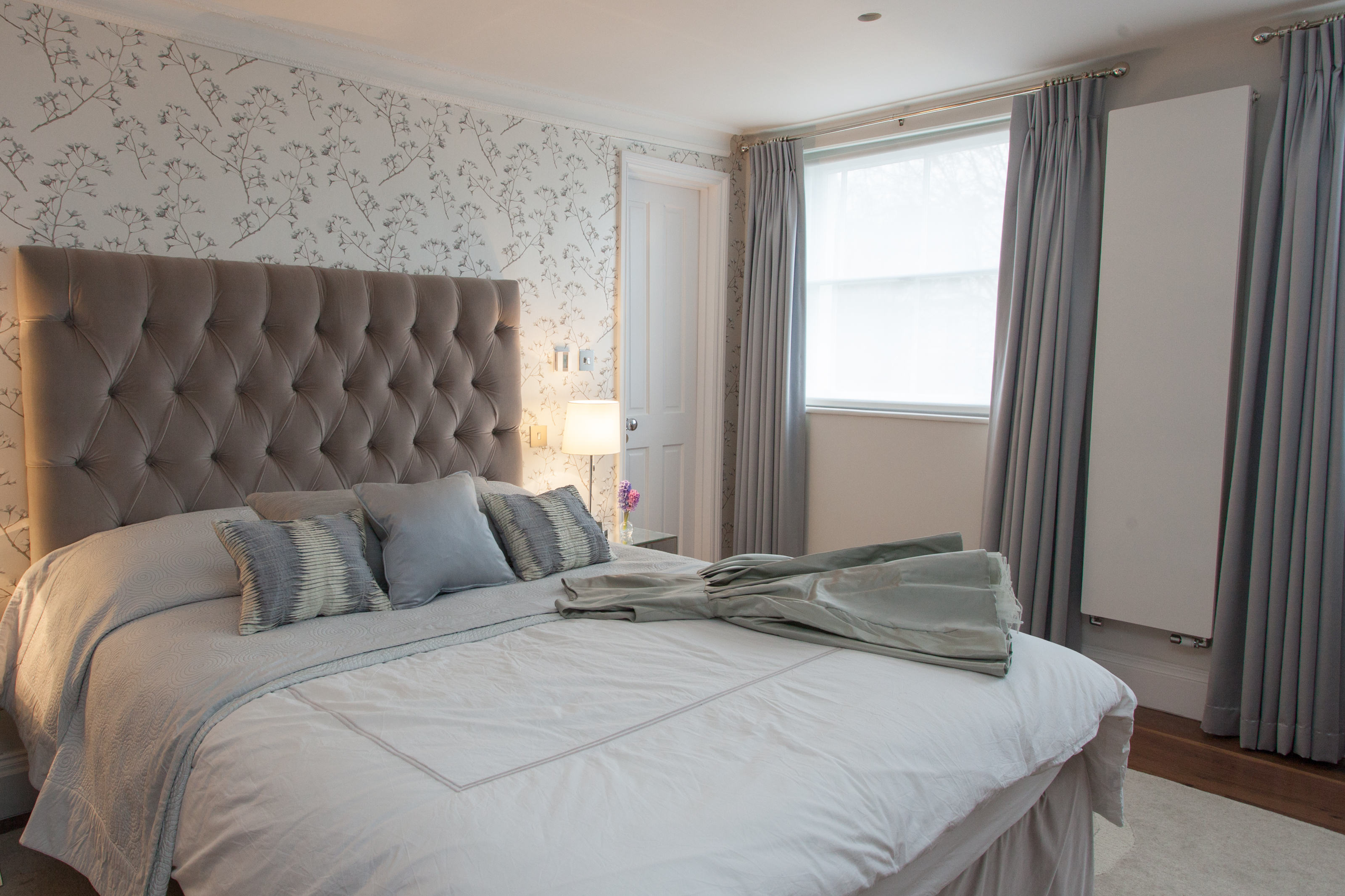 elegant master bedroom in muted colour palette with bespoke headboard and patterned wallpaper