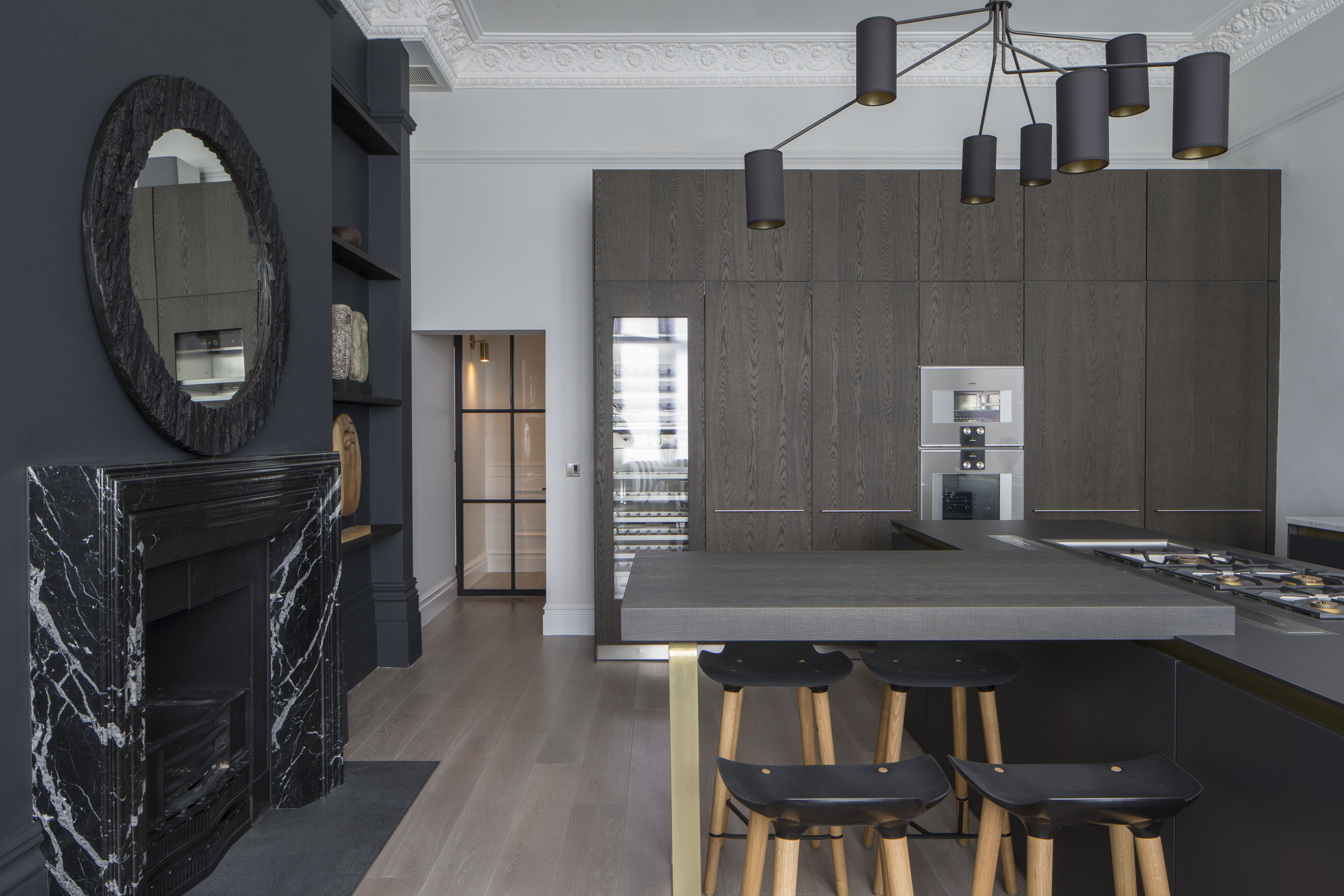 contemporary monochrome kitchen with marble fireplace surround, kitchen island and tall timber cabinetry