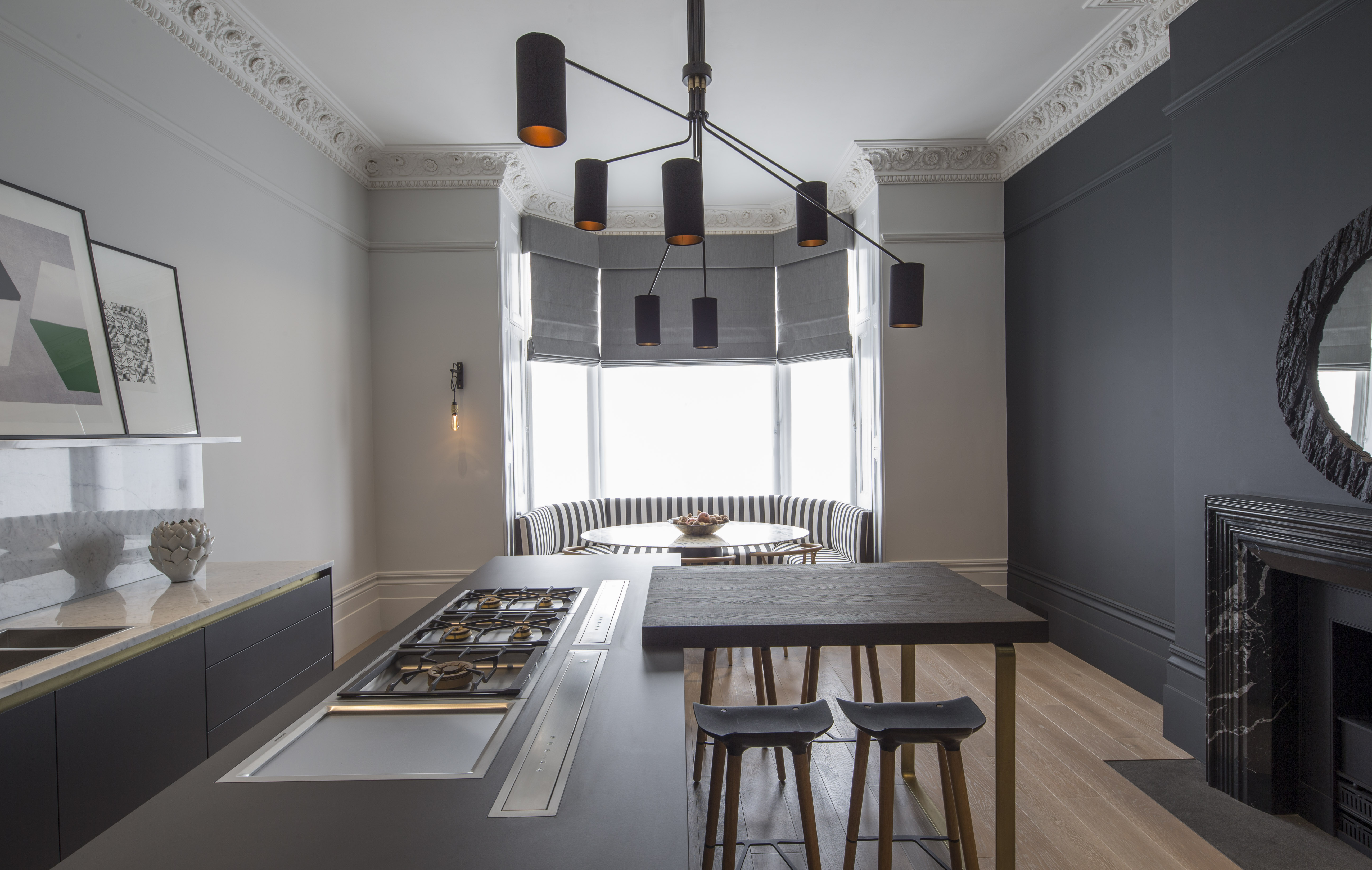 contemporary industrial kitchen with bay window and pendant lighting above kitchen island