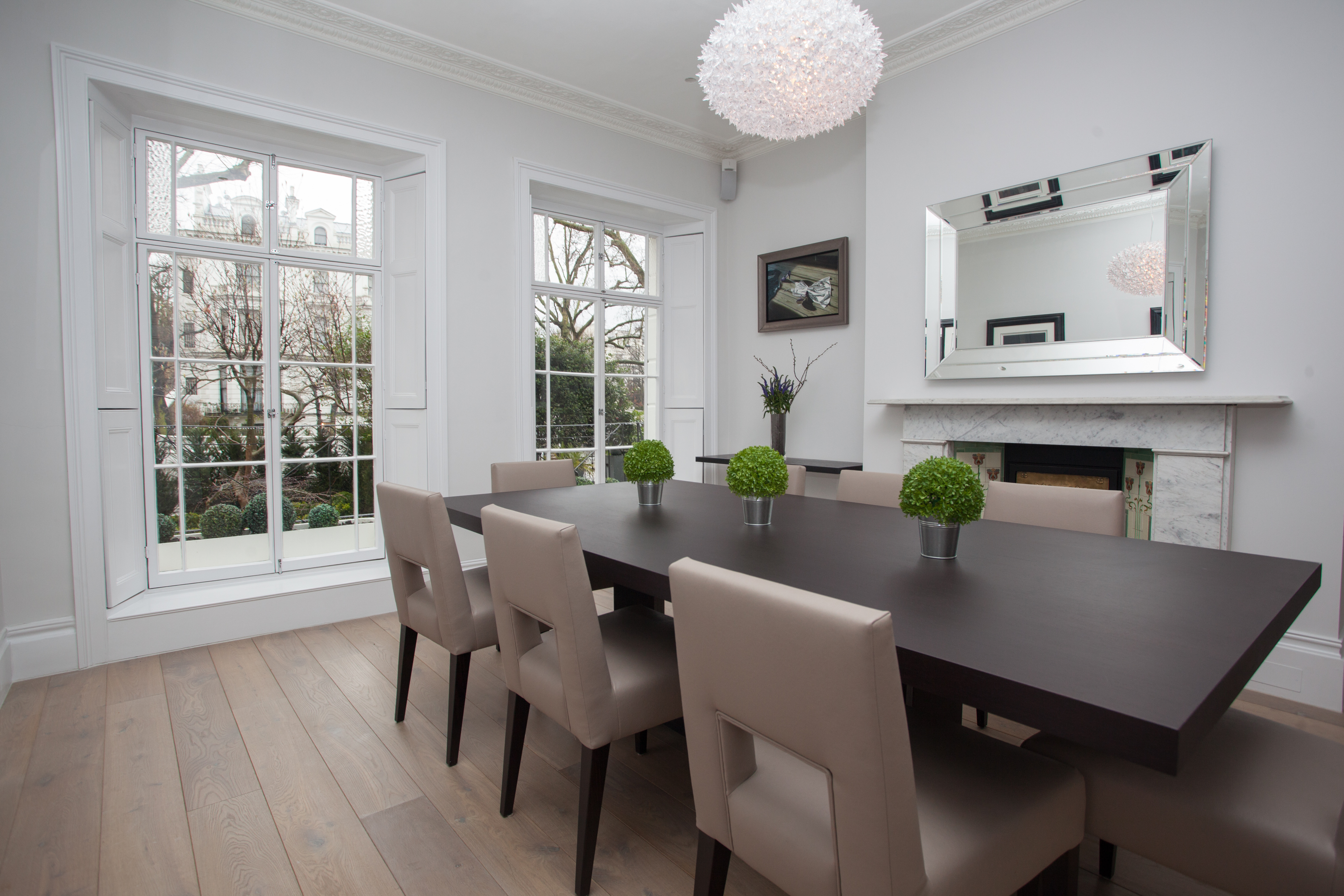 minimalist dining room with large timber dining table and pendant chandelier
