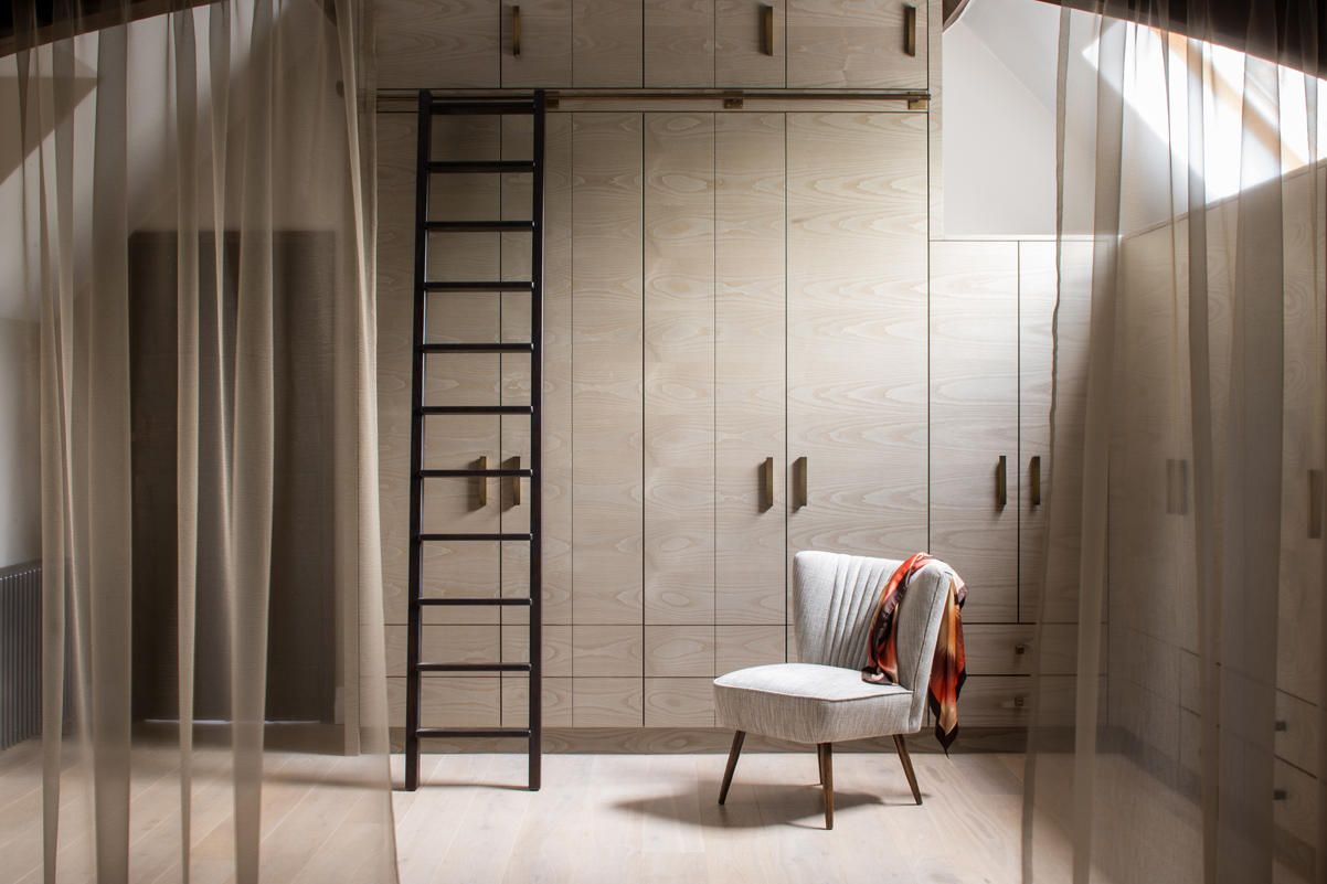 A sheer voile separates the dressing room from the master bedroom. The joinery is fitted into the apex of the ceiling for maximum storage.