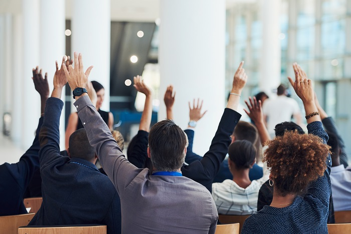 A photo of a group of people with their hands raised in a business meeting