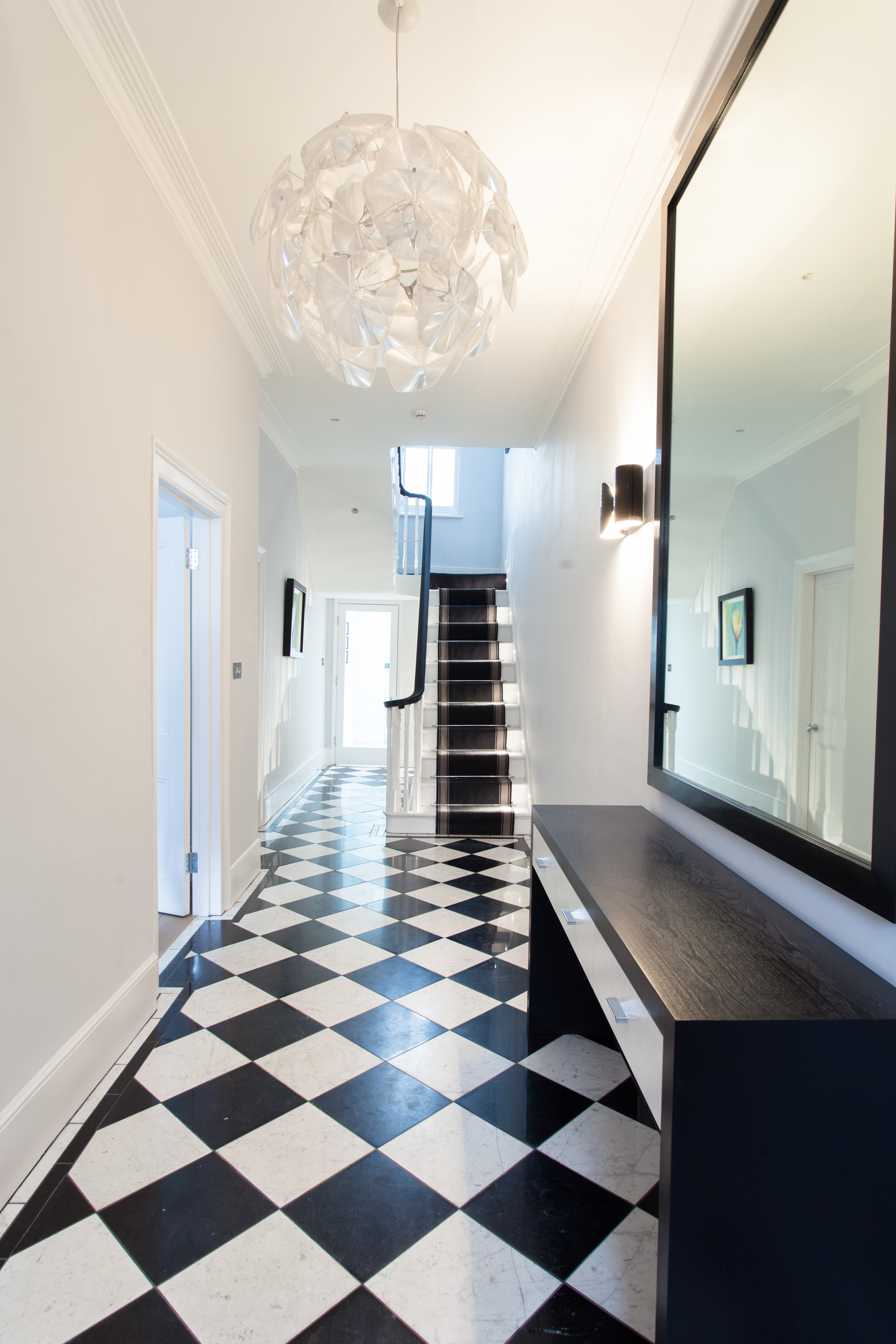 minimalist entrance with black and white floor tiles, dark timber console table and pendant chandelier