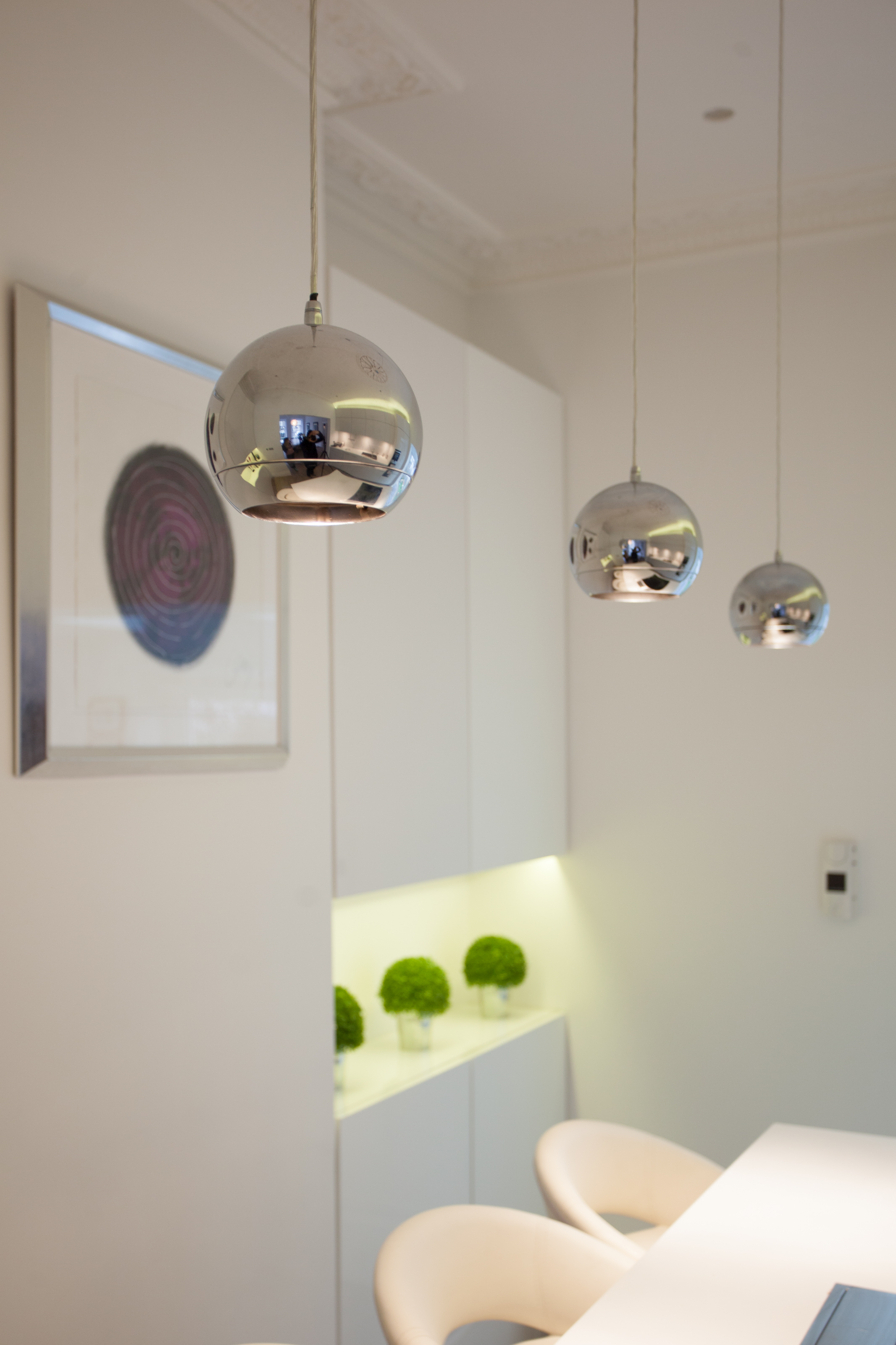 contemporary white kitchen island with pendant lights above kitchen island and contemporary artwork