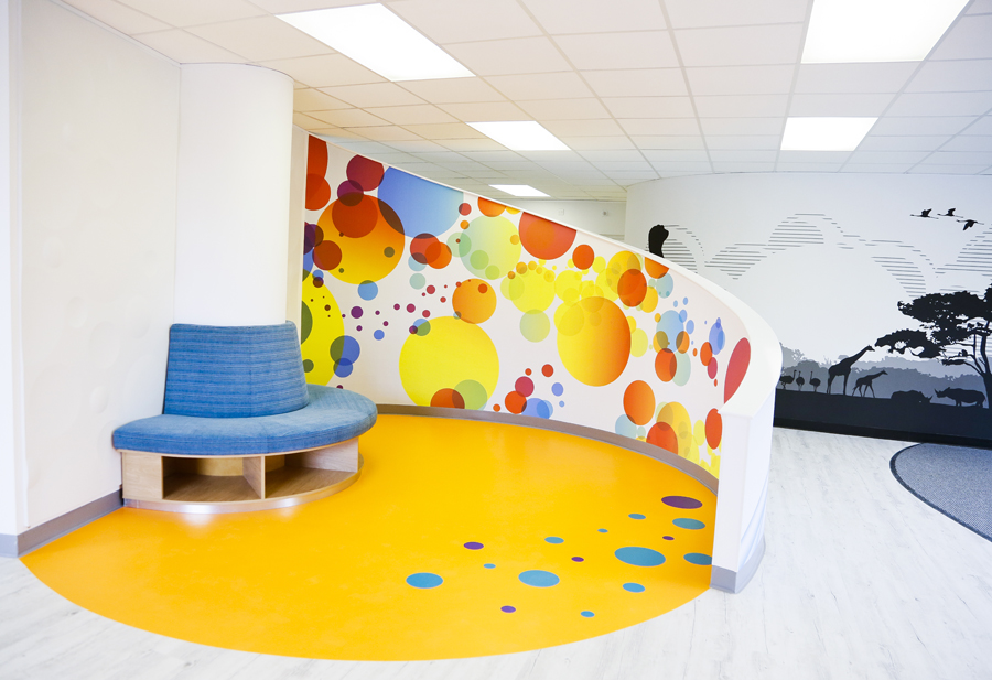 "We designed the Centre Play pod so that children could play on the floor with their toys, do puzzles, read or sit with their parents. The curved wall ""hugs"" the children as they play providing them with protection from the other users of the centre."