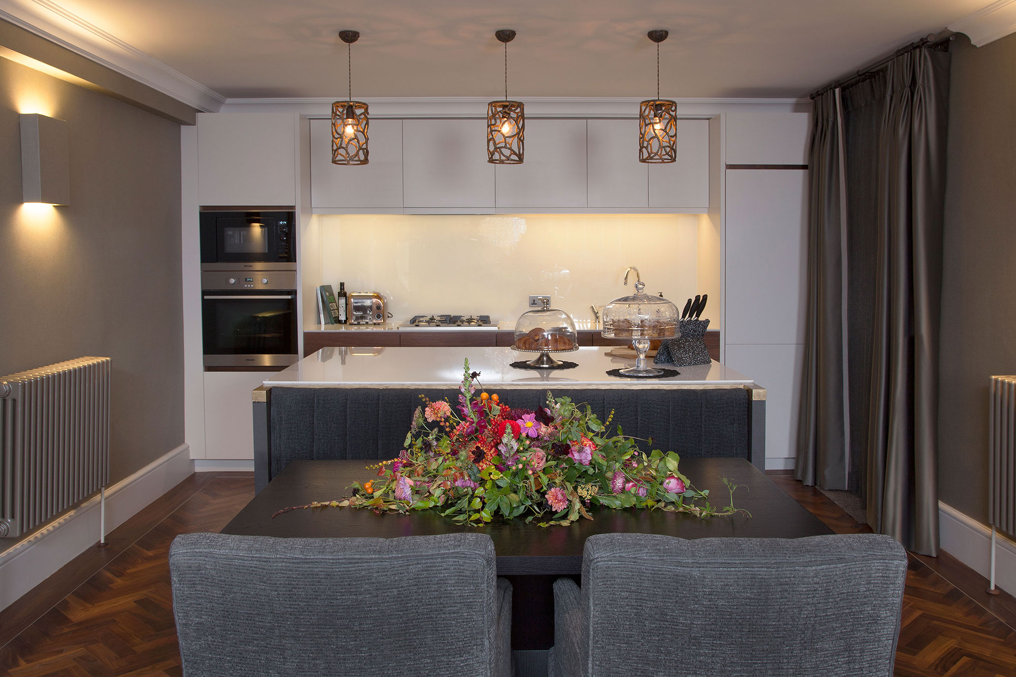 kitchen island with built-in banquette seating and pendant lights above kitchen island