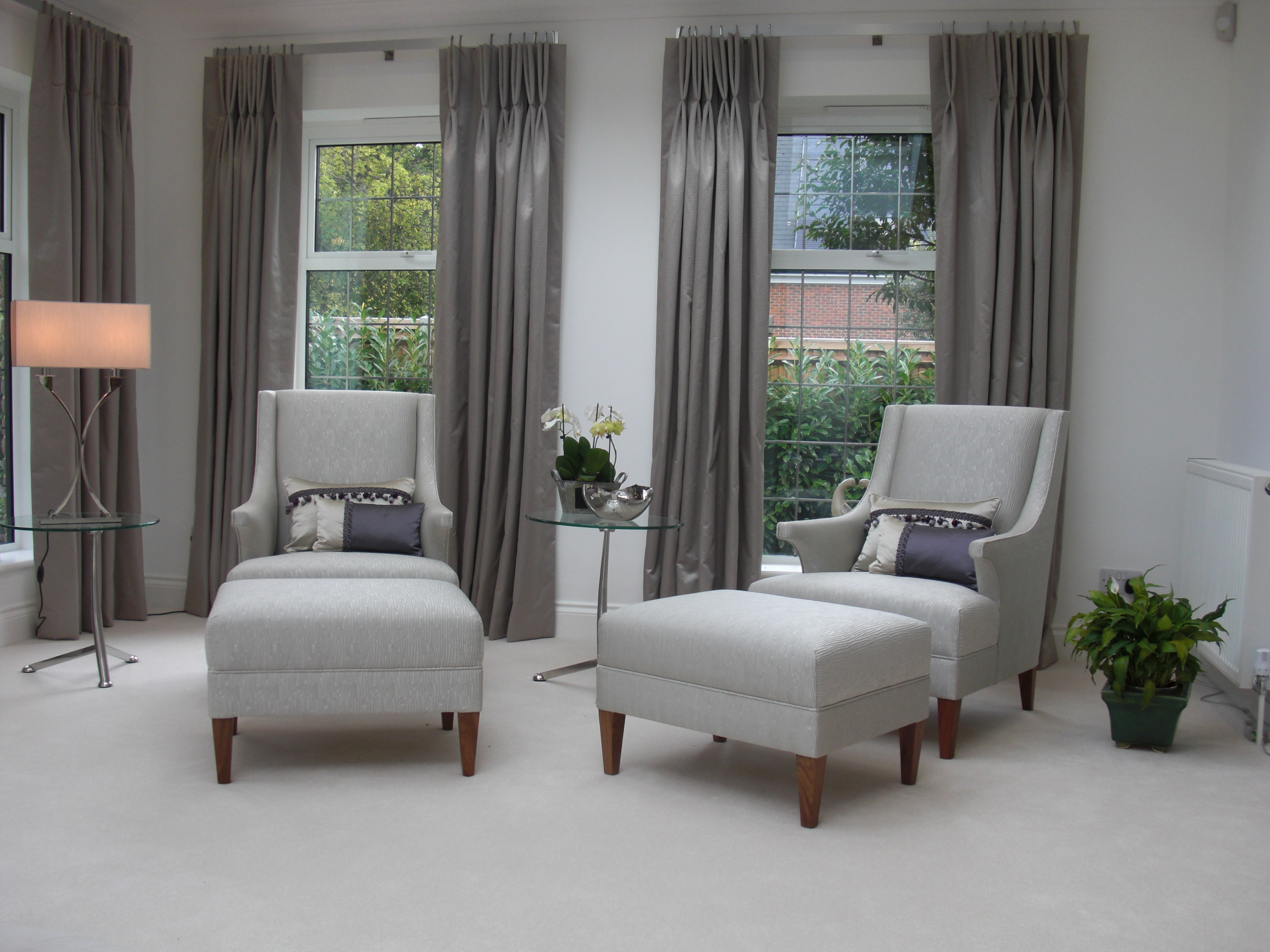 Two armchairs with footstools in the garden end of the room.