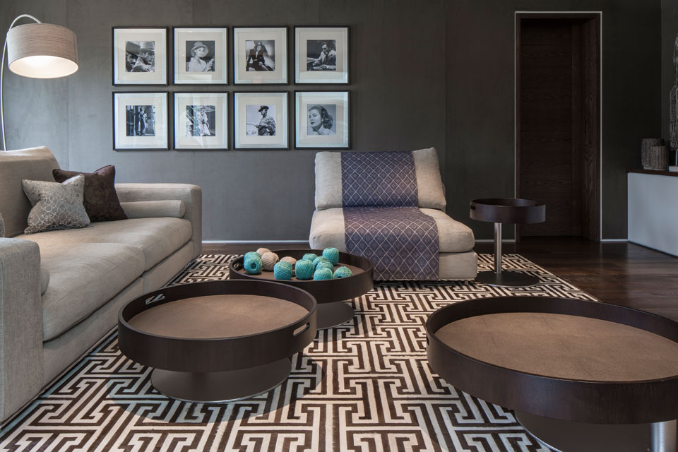 Circular leather clad tray tables are peppered around the cinema room with walls clad in suede