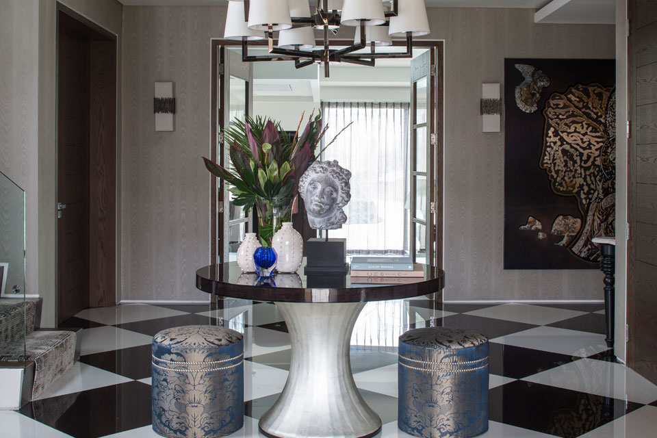 A  bold round table with silver leaf base and high gloss top is centered in the entrance hall of our grand Broad Walk family home