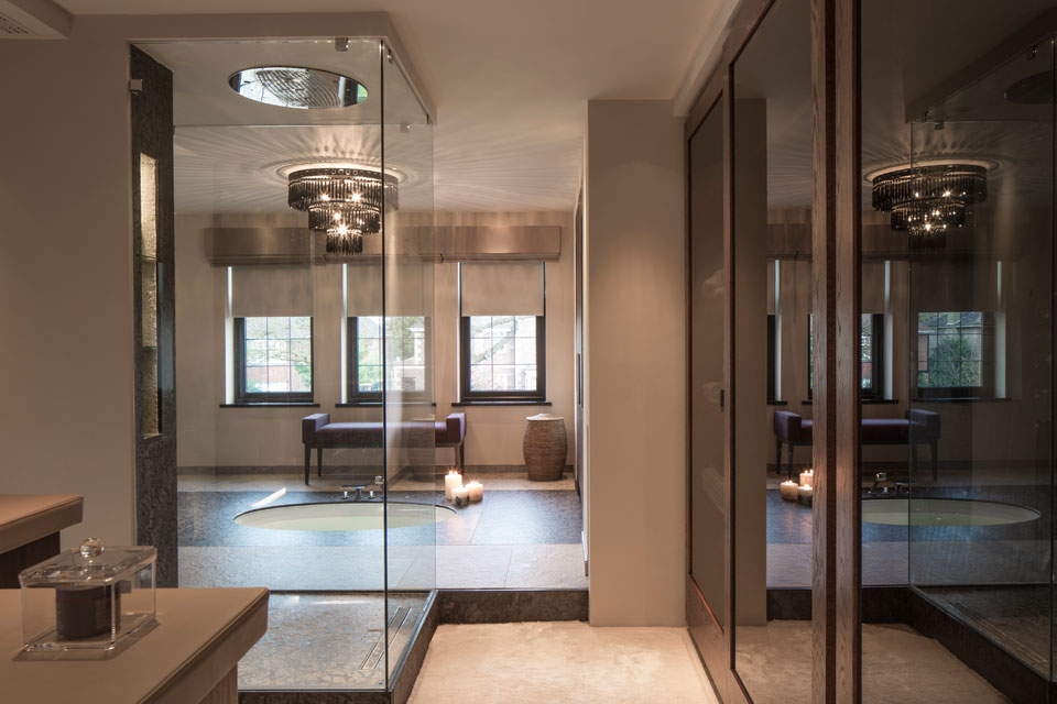 The master bathroom features a sunken bath with large black glass chandelier above for ultimate opulance