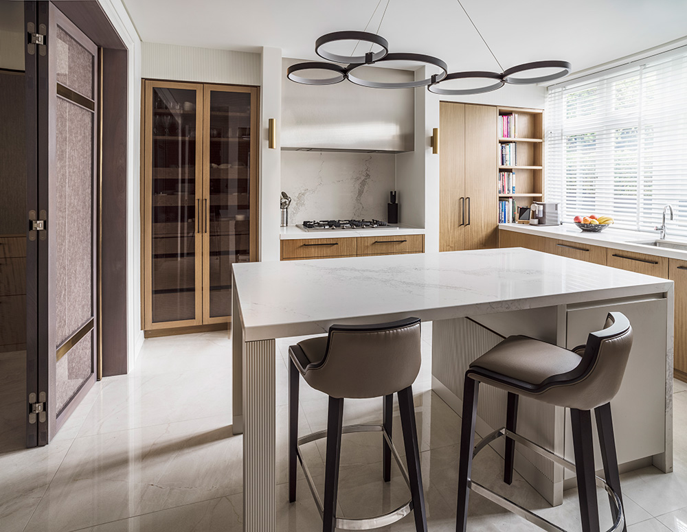 contemporary wood and marble kitchen with circular pendant lighting above kitchen island