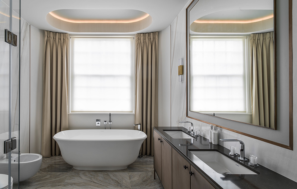 luxury bathroom with large bay window, dress curtains and oval freestanding bath