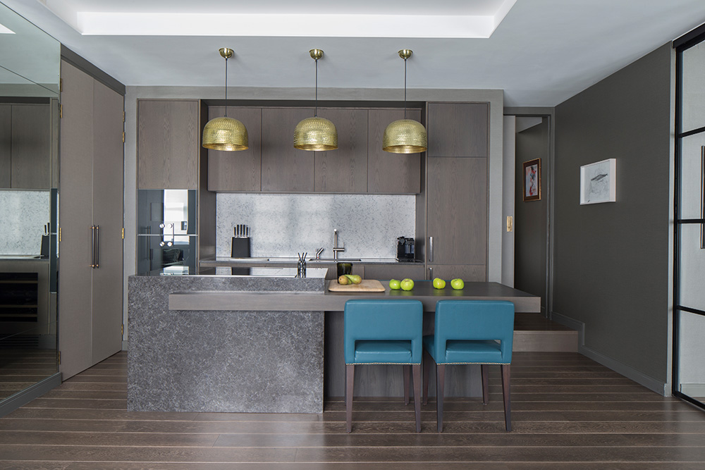 open plan kitchen with timber kitchen island, bronze pendant lights above kitchen island and teal dining chairs