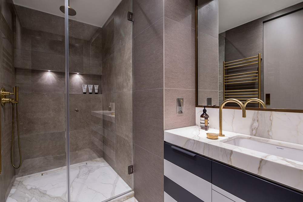luxurious bathroom with marble shower enclosure and grey and white striped bathroom vanity